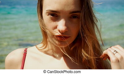 blonde woman with freckles on her face posing on the beach -...