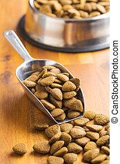 Dry kibble dog food in scoop. - Dry kibble dog food in metal...