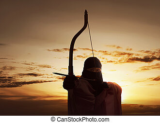 Asian muslim woman wearing hijab holding bow to shoot an arrow
