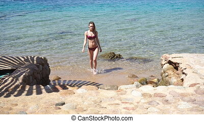 young girl Comes out of the sea on the steps - sexy young...