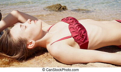 sexy young girl in red swimsuit lying and sunbathing