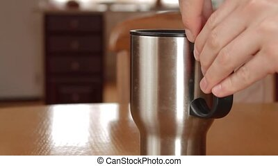 Metal cup with a drink in the room - Man is opening Metal...