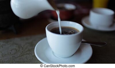 the man sitting at the table pouring milk into coffee