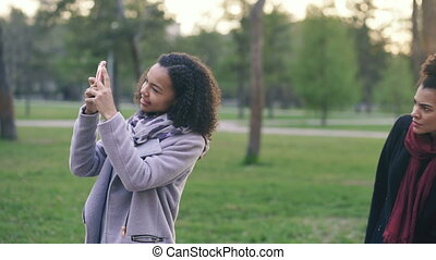 Two attractive mixed race women surpisely have meeting in the park near mall store