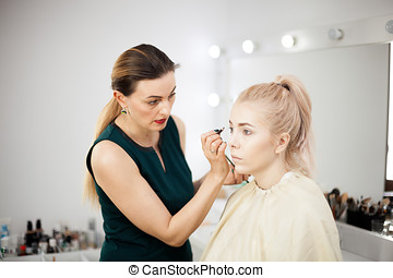 Makeup teacher in a makeup studio with a blonde model
