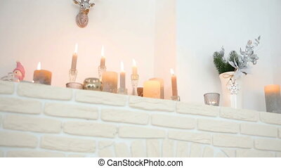 Details of white color in the interior. Decoration with a fireplace and candles