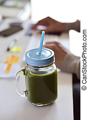 green smoothie on the office desk - closeup of a green detox...