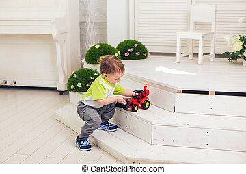 Little boy is playing with toy car at home