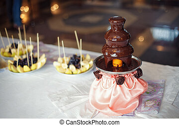 Chocolate fondue fountain with prepared fruits on table
