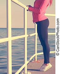 Woman in sportswear standing on dyke sea no face - Outdoor...