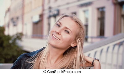 Portrait of young blonde woman standing in the street....