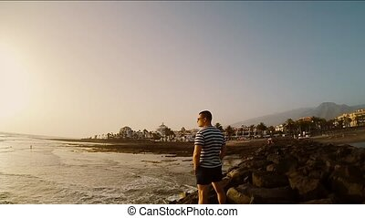 Young tourist man standing standing on the coast by the sea in windy day. Male looking to the beautiful sunset.
