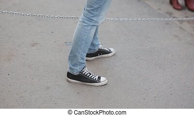 Close up view of male legs wearing in sneakers. Teenager spending time outside, touching a chain.