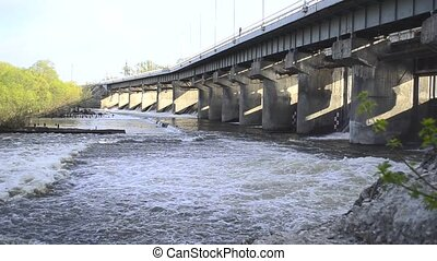 Spring flood water flowing on hydroelectric power station...