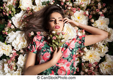 Portrait of beautiful sexy woman lying down on flowers