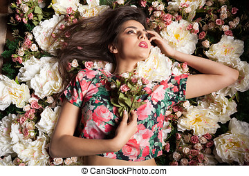 Portrait of sexy woman lying down on flowers