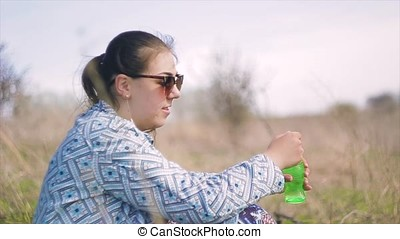 girl with glasses outdoors blow bubbles