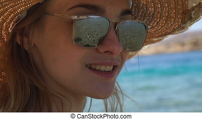a young girl wearing a hat and glasses through which you can...