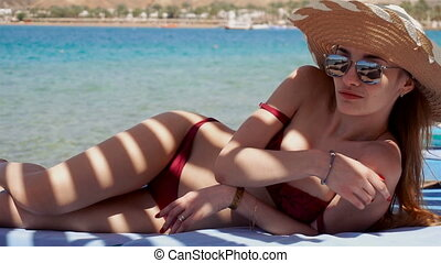 girl in swim suit glasses and a hat is lying on the beach near the sea in the shade and smiles