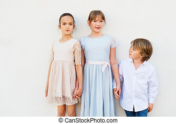 Group of three kids, 2 girls and one boy, wearing party clothes, standing against white background