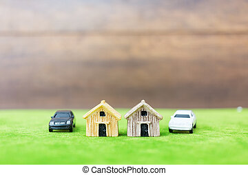 Miniature bamboo house and car on green yard