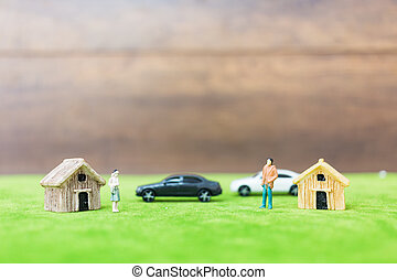 Miniature bamboo house and couple on green yard