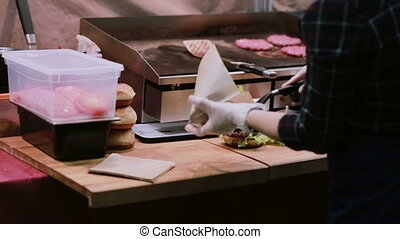 A chef in white gloves putting every burger into package for...