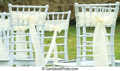 Wedding white chairs decorated with silk ribbons