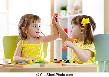 Two cute little girls playing together in daycare