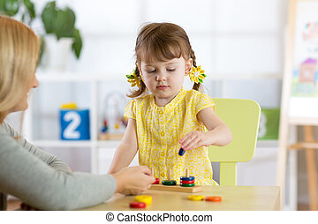 kid and mother playing together with puzzle toy