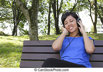 Woman listening to music - An Asian woman listening to music...