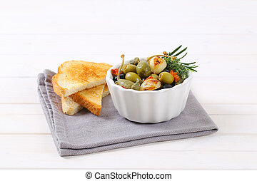 pickled olives, capers and caper berries with toast