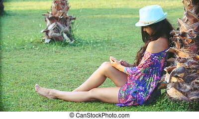 young tanned woman with long hair sitting under tropical palm trees in summer. she uses smartphone