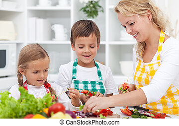 Closeup of young kids with their mother in the kitchen