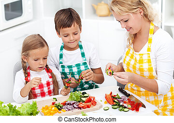 Happy young kids with their mother in the kitchen, top view closeup