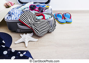 Bikini and clothes in luggage on the laminate floor