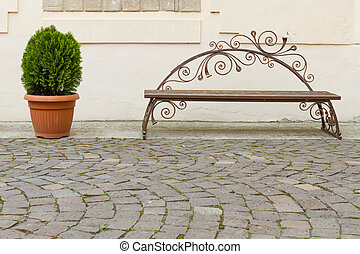 Beautiful decorative bench and flower pot with cobblestone