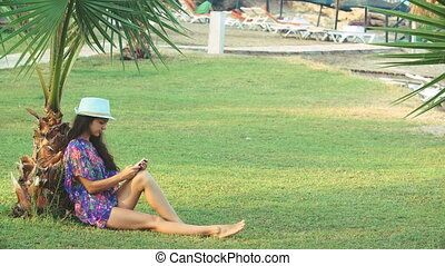 young tanned woman with long hair sitting under tropical...