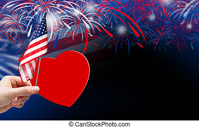 Hand holding red paper heart and USA flag on fireworks...