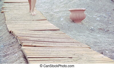 beautiful female tanned feet walking along wooden walkway on...