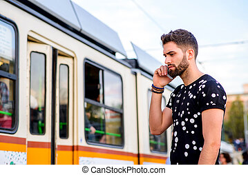 Young hipster man in a tram station