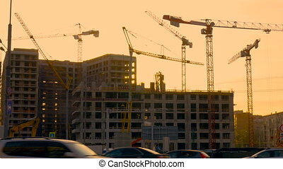 Construction site. During the sunset. Work of tower cranes....