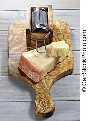 Italian hard cheese with grater on wooden background