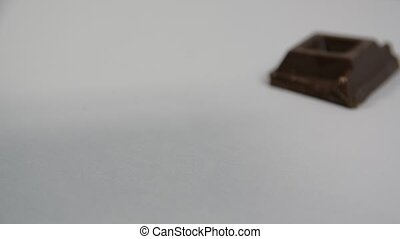 Pieces of chocolate bar falling on neutral background -...