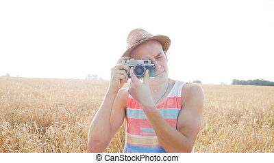 Young man photographing with vintage camera. - Young hipster...