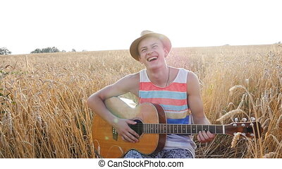 Young man with acoustic guitar at the wheat field.