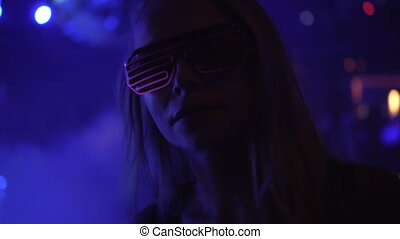 Woman dancing in the club wearing neon led glasses