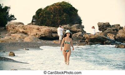 young beautiful tanned woman with long hair in bikini...