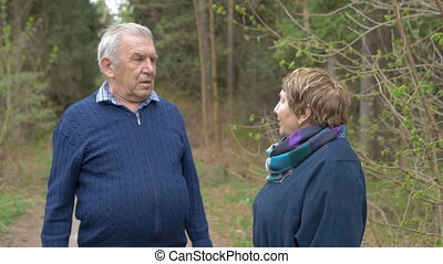 An adult couple talking on a walk in the park. Swear, find out the relationship.