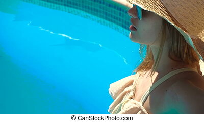 a young girl wearing a hat and glasses stands in a swimsuit in pool water